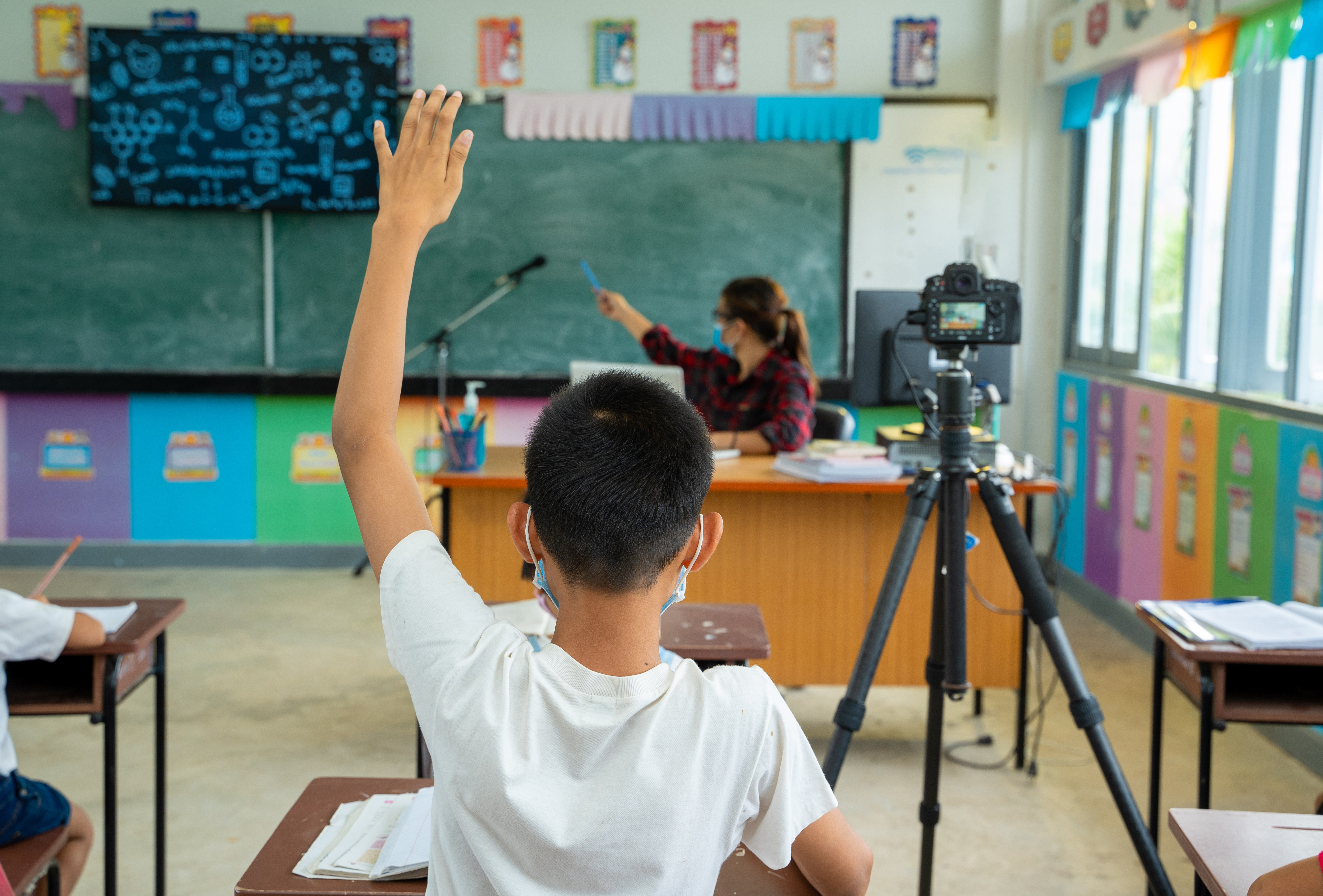 A child wearing a facemask raises his hand in a classroom. A video camera to include children learning remotely is at his right.