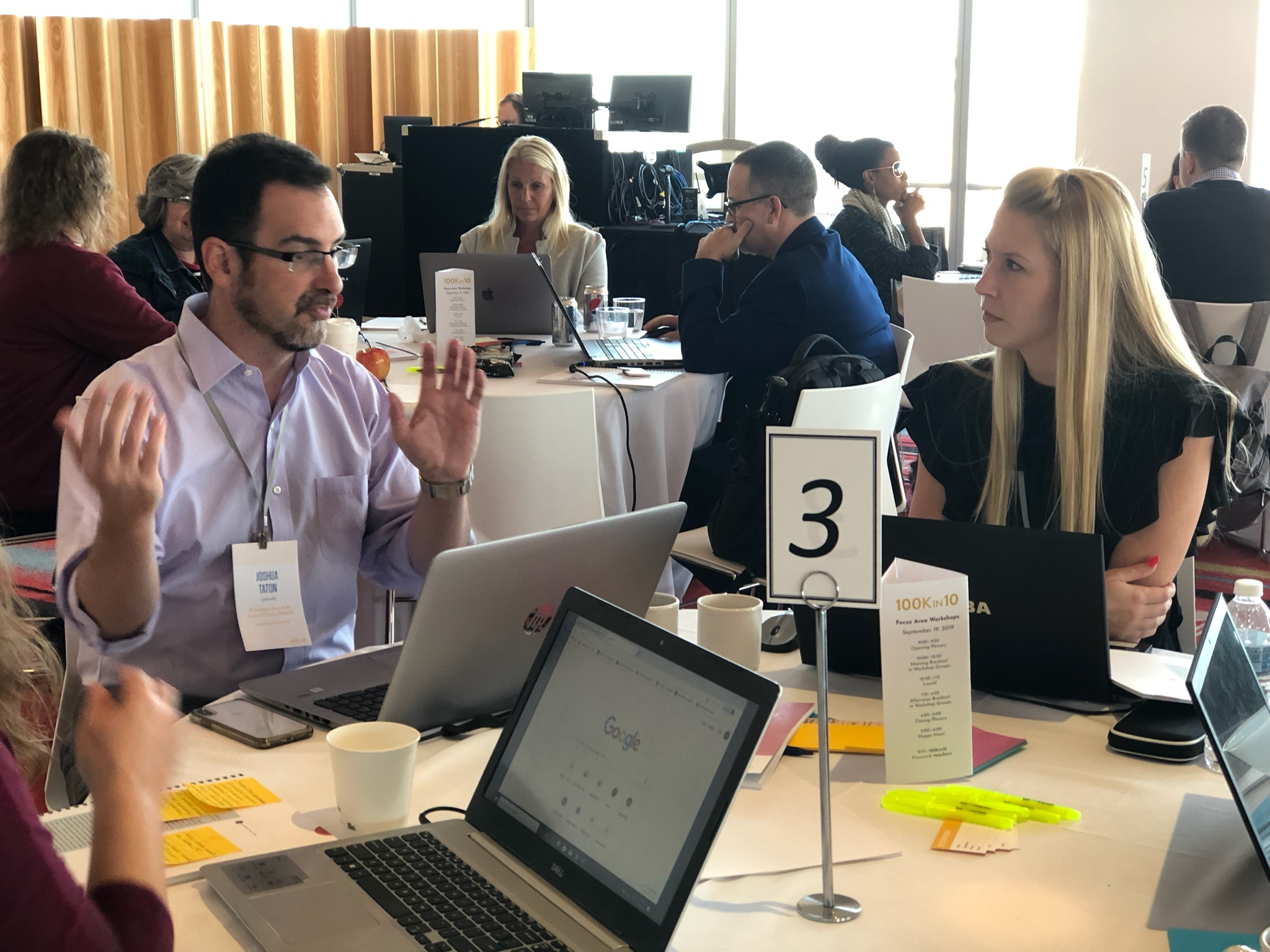 Lindsay M. Anderson of ASSET in discussion with a group of math educators at a table during recent 100kin10 gathering in NYC